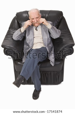 Senior man sitting in an armchair and putting on his glasses. - stock photo