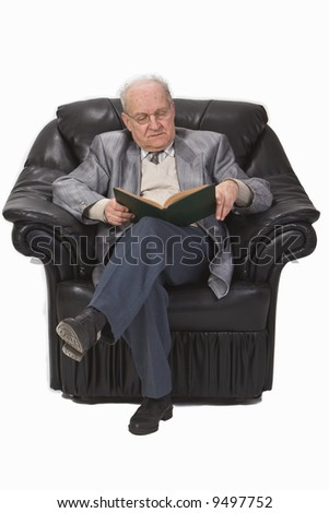 Senior man sitting in an armchair and reading a book.