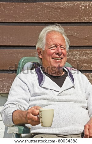 Senior man sitting in garden in chair in summer sun.