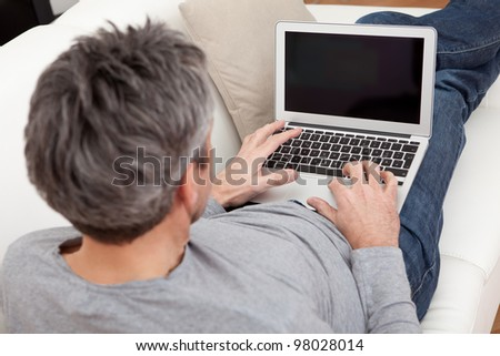 Senior man sitting in sofa at home and using laptop