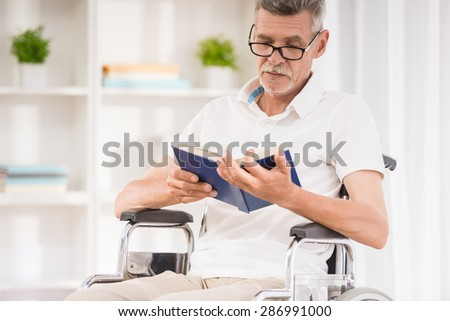 Senior man sitting in wheelchair and reading a book at home. - stock photo