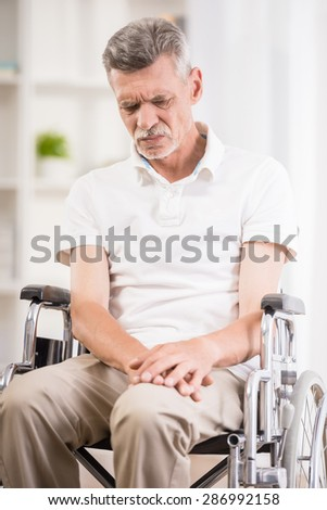 Senior man sitting in wheelchair at home. - stock photo