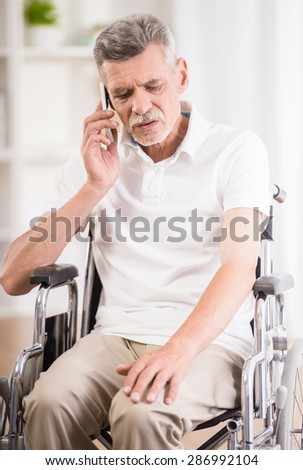 Senior man sitting in wheelchair at home and talking on phone. - stock photo