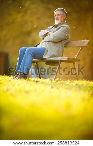 Senior man sitting on a bench in a park, enjoying retirement - stock photo