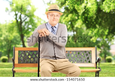 Senior man sitting on a wooden bench and looking at camera, in a park - stock photo