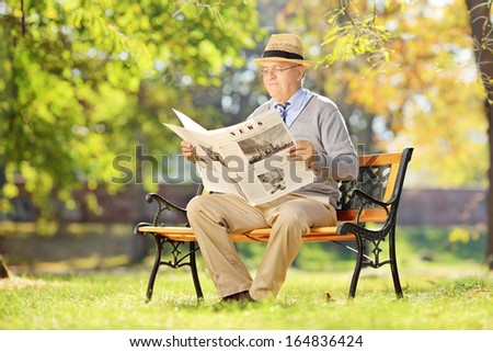 Senior man sitting on a wooden bench and reading a newspaper in autumn  - stock photo