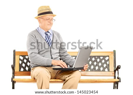 Senior man sitting on a wooden bench and working on a laptop isolated on white background - stock photo