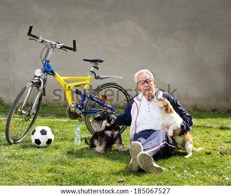 Senior man sitting on grass with dogs after bike ride