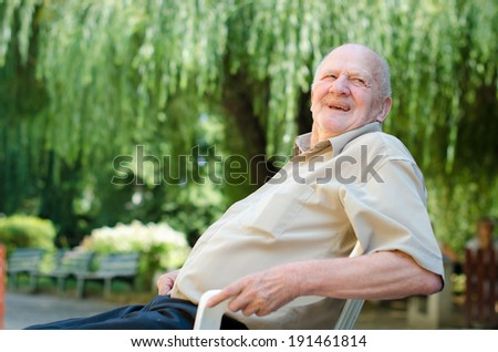 Senior man sitting outdoor and smiling - stock photo