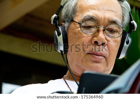 Senior man sitting outside reading E-book on his tablet.  - stock photo