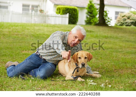 Senior man sitting with dog in garden in front of the house - stock photo
