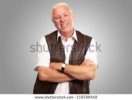 Senior Man Smiling With Hands Folded Isolated On Gray Background - stock photo