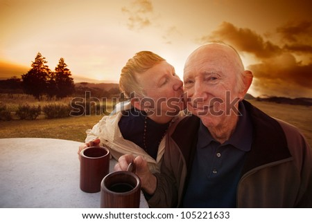 Senior man smirks while lady kisses him outside in field