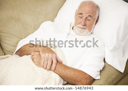 Senior man sound asleep on the couch, suffering from a cold. - stock photo