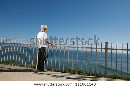 Senior man standing above the ocean looking out to ocean - stock photo