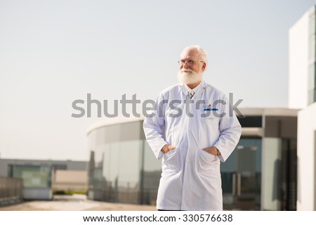 Senior man standing in lab coat at his research center - stock photo