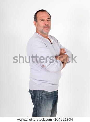 Senior man standing on white background with arms crossed - stock photo