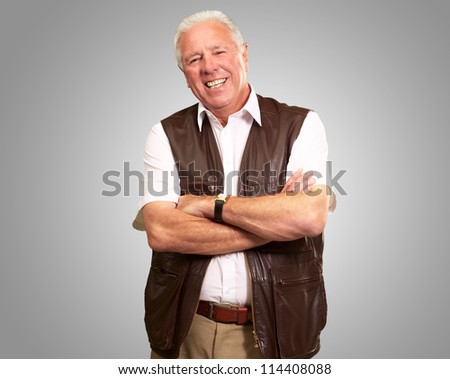 Senior Man Standing With Arms Crossed On Gray Background - stock photo
