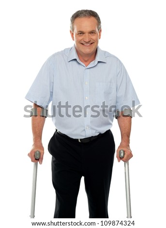 Senior man standing with support of crutches isolated against white background - stock photo