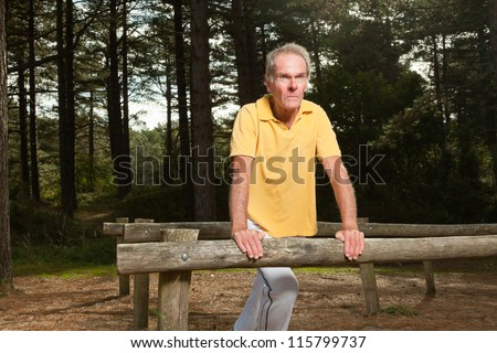 Senior man stretching his leg. Doing workout in nature. Healthy living. Forest. Outdoors. Yellow shirt and white pants. Short grey hair.