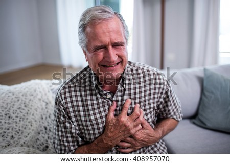 Senior man suffering from heart attack at home - stock photo