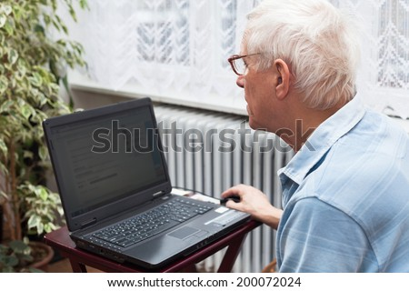 Senior man surfing on the internet at home. - stock photo