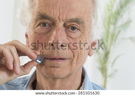 Senior man tacking  homeopathic medicine - stock photo