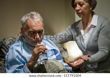Senior man taking medication with water caring wife helping - stock photo