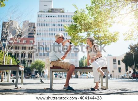 Senior man taking photos of his woman. Mature couple having fun on their holiday. - stock photo