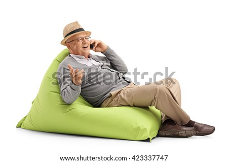 Senior man talking on his cell phone seated on a green beanbag isolated on white background