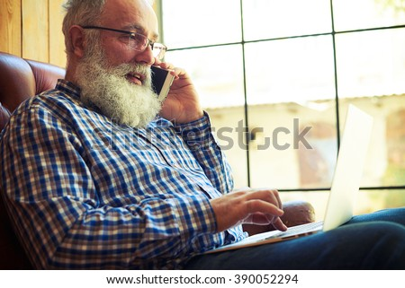 senior man talking on the smartphone and working with laptop at home