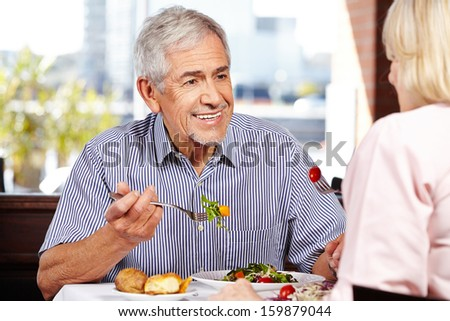 Senior man talking to woman while eating in a restaurant - stock photo