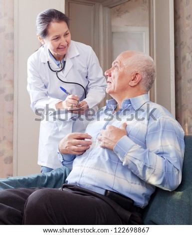 Senior man tells the mature doctor the symptoms of malaise on couch.