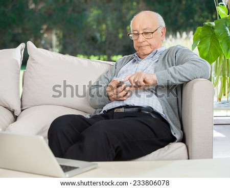Senior man text messaging through smartphone on couch at nursing home porch - stock photo