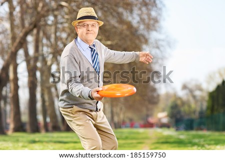 Senior man throwing a frisbee disk in a park - stock photo