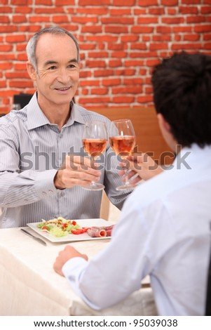 senior man toasting with someone younger
