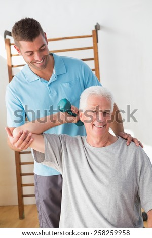 Senior man training with his coach in fitness studio - stock photo