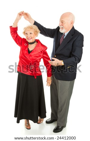 Senior man twirls his wife as they dance together.  Full body isolated on white. - stock photo