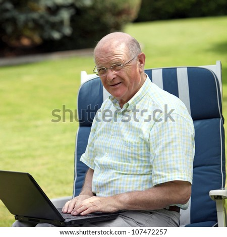 Senior man typing on a laptop Senior man wearing glasses sitting on a comfortable garden chair typing on a laptop