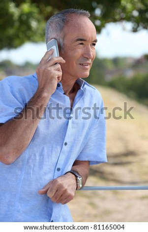 Senior man using a cellphone - stock photo