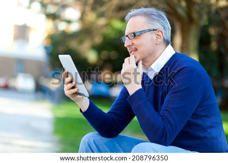 Senior man using a digital tablet outdoor in the park - stock photo
