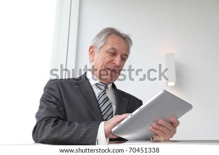Senior man using electronic tab in building hall - stock photo