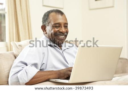 Senior Man Using Laptop At Home - stock photo