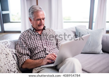 Senior man using laptop in living room at home