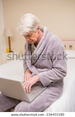 Senior man using laptop on bed at home in bedroom