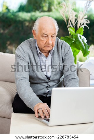 Senior man using laptop while sitting on couch at nursing home porch - stock photo