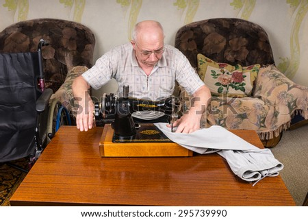 Senior Man Using Manual Old Fashioned Sewing Machine to Mend Pants at Home in Living Room - stock photo