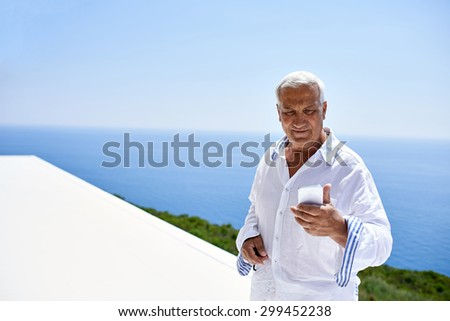 senior man using smart phone outdoor with ocean view background - stock photo