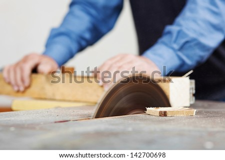 Senior man using table saw for cutting wood at workshop - stock photo