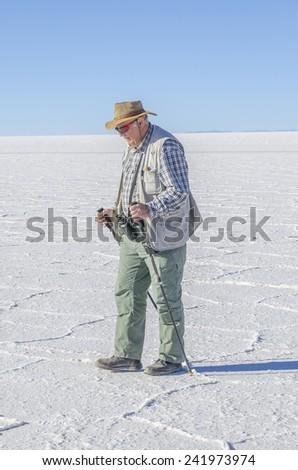 Senior man visiting Salar de Uyuni, Bolivia - stock photo